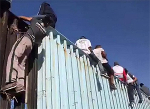 Illegal Aliens scale U.S. border fencing