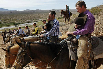 Men on horseback pause for the National Anthem while gathering to support the Bundy family in its challenge against the Bureau of Land Management